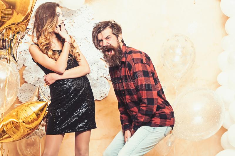 Sensual woman and bearded man smile with balloons, christmas. Hipster and woman on new year or xmas eve. Couple in love stock images