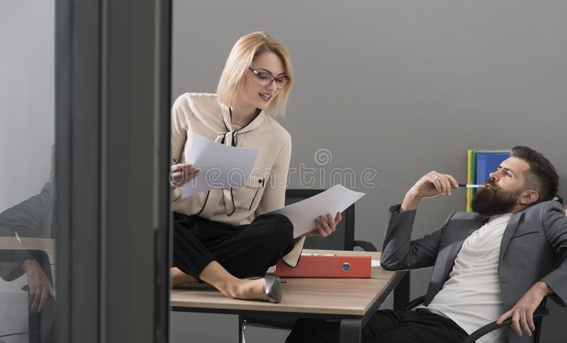 Sensual woman and bearded man work together in office. Businesswoman and businessman write business plan. Concentrated. Sensual women and bearded men work stock images