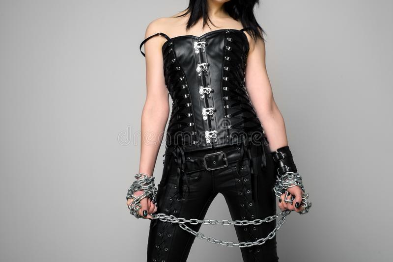 Sensual woman in black leather corset and pants with chain in hand. Image royalty free stock photography