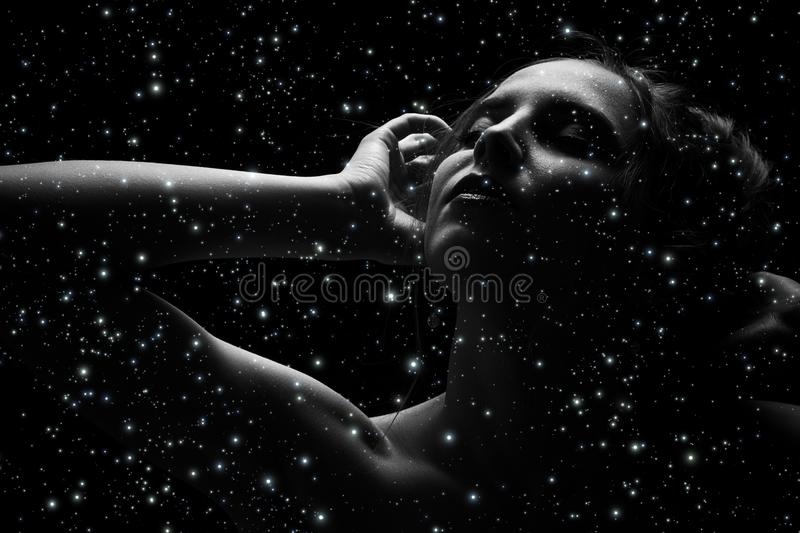 Sensual young woman. Sensual woman, closed eyes on stars sky background image with double exposure royalty free stock image