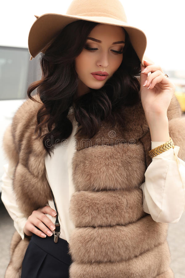 Sensual woman with dark hair in elegant clothes and luxurious fur coat. Fashion outdoor photo of gorgeous sensual woman with dark hair in elegant clothes and stock photo