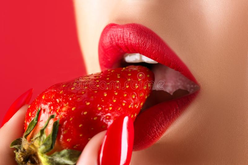 Sensual woman eating strawberry close up isolated stock photos