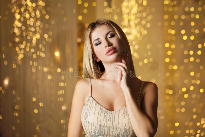 Sensual woman on golden party glitter background stock photo