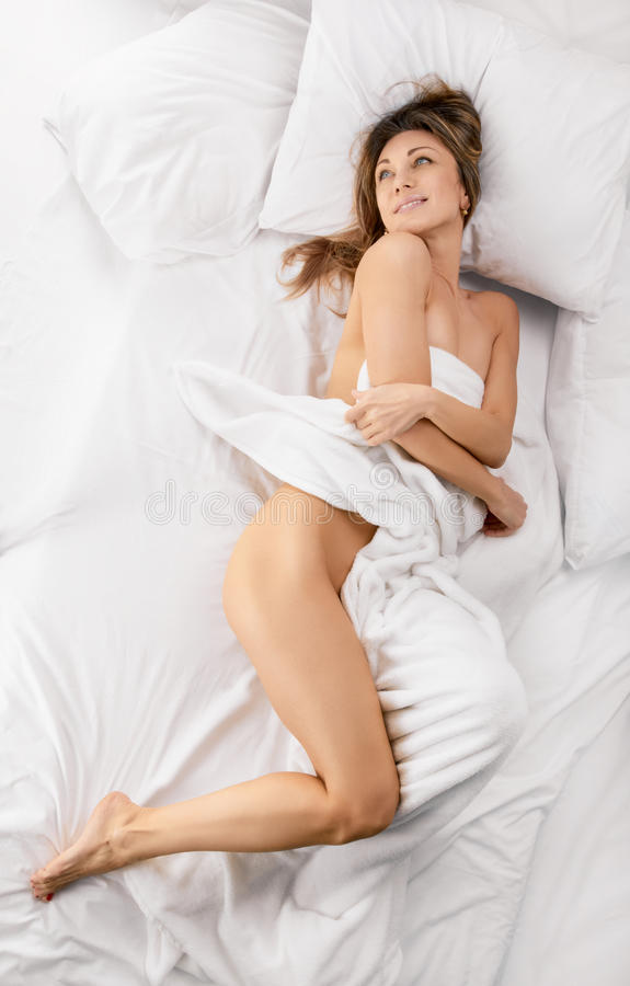 Sensual woman laying in bed stock photography