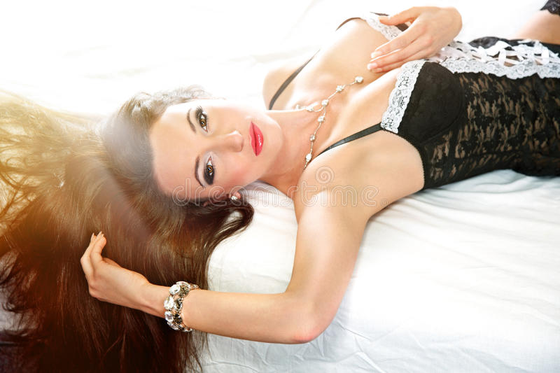 Sensual woman with long brown hair lying on bed royalty free stock photos