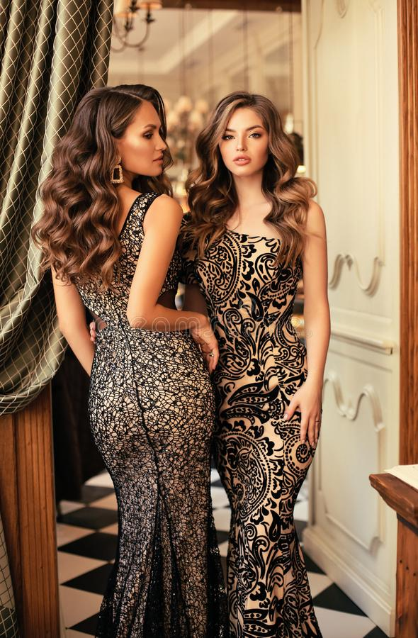 Sensual woman with long curly hair in luxurious dresses posing i stock photo