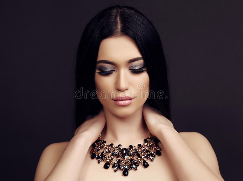 Sensual woman with long dark hair with luxurious bijou necklace. Fashion studio photo of beautiful sensual woman with long dark hair and bright makeup, with royalty free stock photography