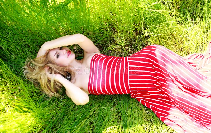 Sensual woman in long summer dress lies in green grass royalty free stock images