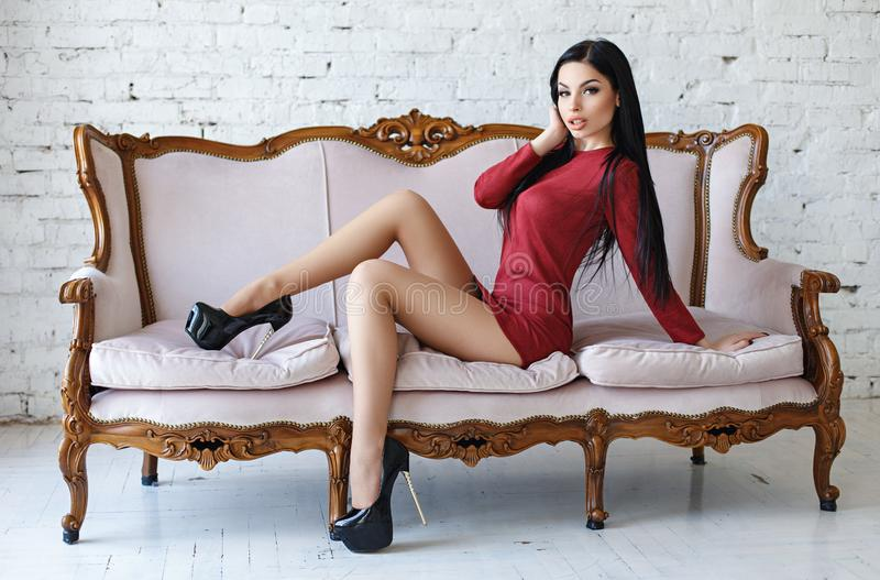 Sensual woman with perfect body posing in a red short dress stock photography