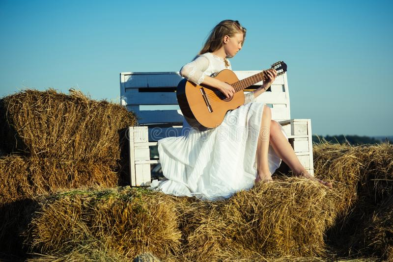 Sensual woman play guitar on wooden bench. Woman guitarist perform music concert. Albino girl hold acoustic guitar. String instrument. Fashion musician in royalty free stock image