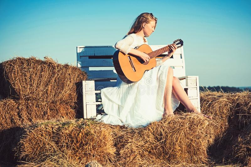 Sensual woman play guitar on wooden bench. Woman guitarist perform music concert. Albino girl hold acoustic guitar royalty free stock photo