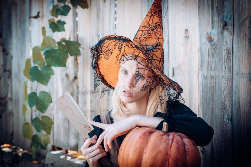 Sensual woman is preparing to carving a pumpkin. Witch posing with Pumpkin. Gothic woman in witch halloween costume with. Witch posing with Pumpkin on wood royalty free stock images