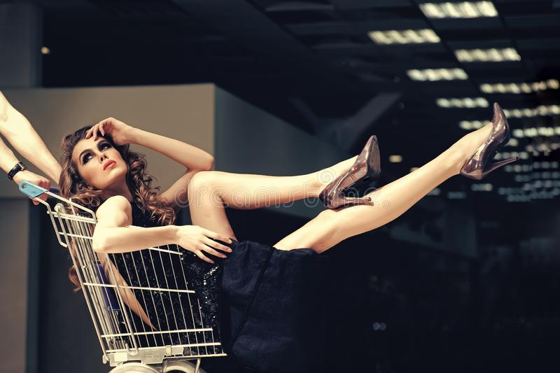 Sensual woman sit in shopping cart stock photography