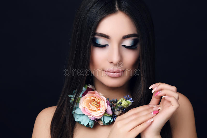 Sensual woman with straight black hair with bright makeup and flower's necklace. Fashion portrait of beautiful sensual woman with straight black hair with bright stock images