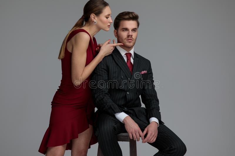 Sensual woman touching her lover`s face while he sits. Sensual women touching her lover`s face while he sits on a stool on grey background stock images