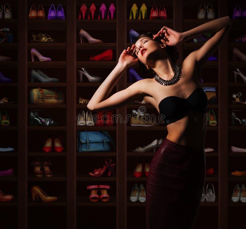 Sensual Woman in Wardrobe with Plenty of Footwear. Pretty Dreamy Woman with Footgear stock photography