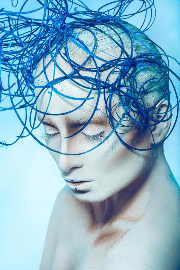 Sensual woman with white body art in studio. On blue background stock images