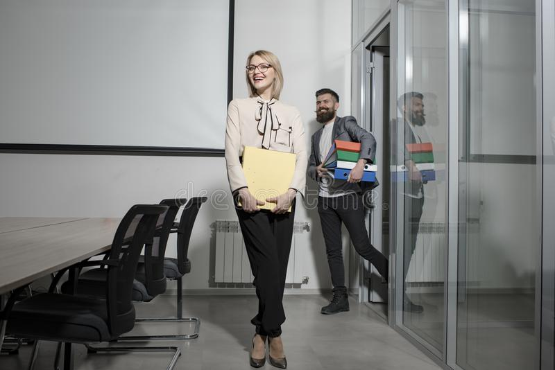 Sensual woman and bearded man smile in office. Happy business woman and man hold file folders. Paperwork and business. Sensual women and bearded men smile in royalty free stock photos