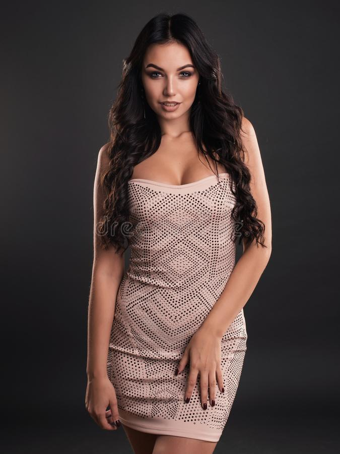 Sensual young brunette woman in beige dress isolated on gray background stock photo