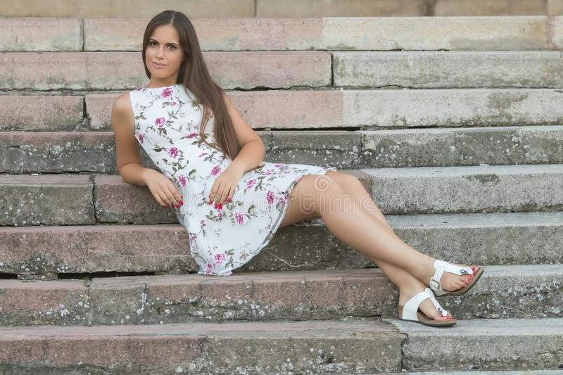 Sensual young brunette woman portrait outdoors sitting on stairs royalty free stock images