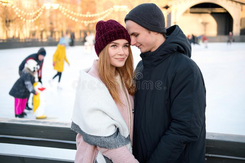 Young couple in love holding hands touching noses enjoying romantic moment together outdoors near ice rink in winter stock image