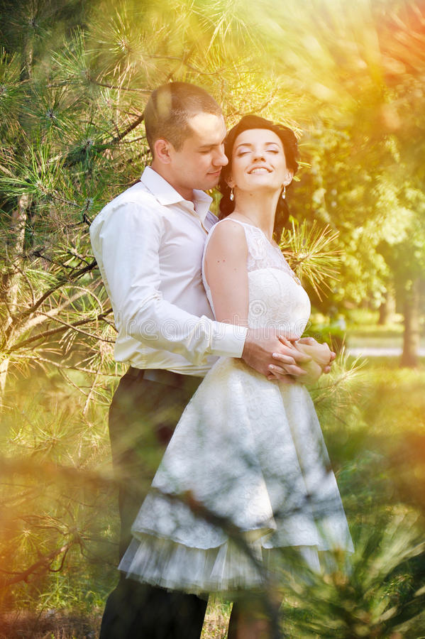 Sensual young couple in love outdoor in blossom evening sunlight with flares. And they feeling happy stock photo