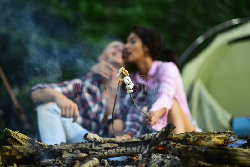 Sensual young couple in love roasting sweet marshmallow in fire and have fun together. Man and woman relaxing near stock photos
