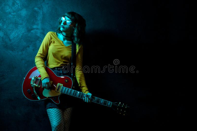 Sensual young hipster woman with curly hair with red guitar in neon lights. Rock musician is playing electrical guitar stock image