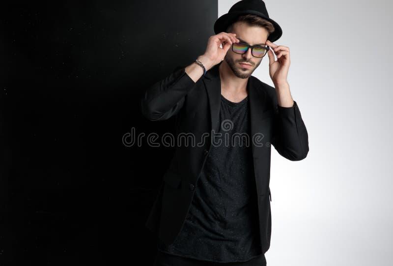 Sensual young man fixing glasses in studio stock photos