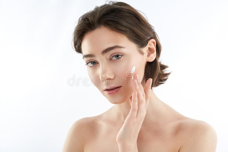 Sensual young woman applying cream on face royalty free stock photos