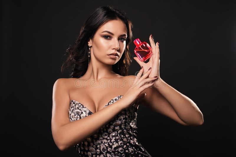 Sensual young woman in a beautiful dress with perfume on dark background royalty free stock photos
