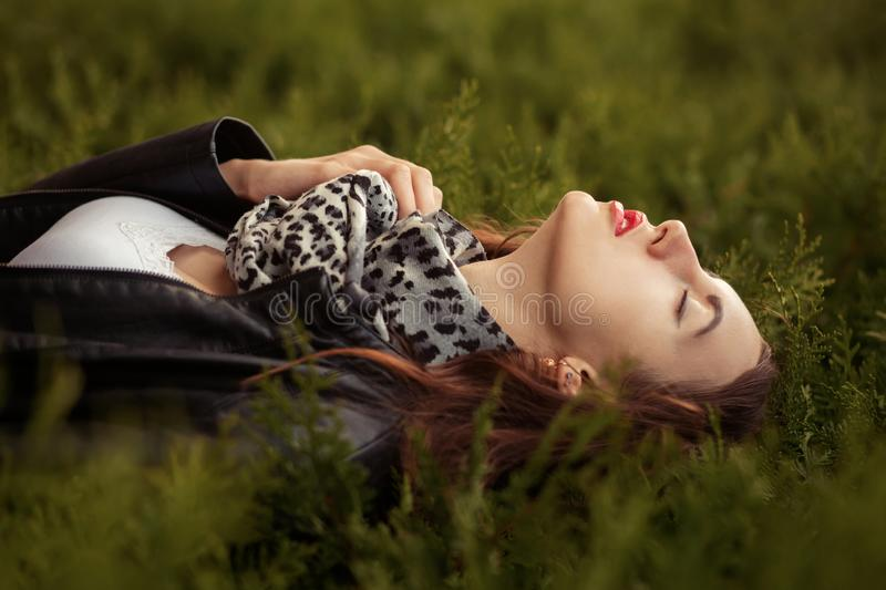 Sensual young woman in leather coat lying on green grass stock photography