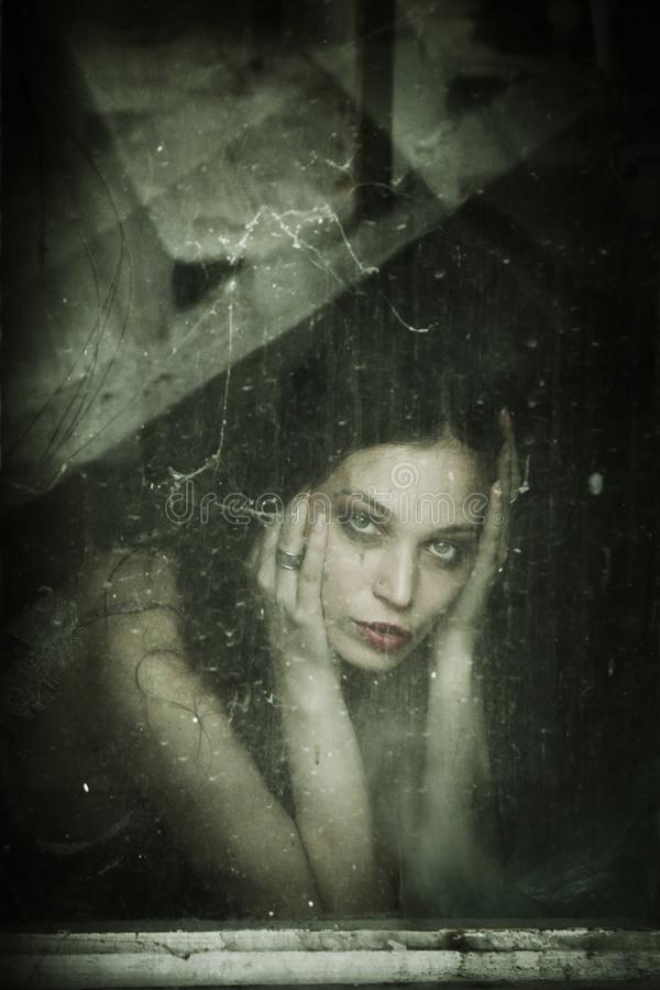 Sensual young woman portrait behind old dirty window. Sensual young woman portrait behind old window royalty free stock images