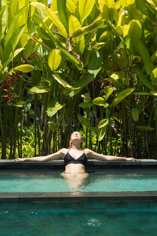 Sensual young woman relaxing in outdoor spa infinity swimming pool surrounded with lush tropical greenery of Ubud, Bali. Wellness, natural beauty and body care royalty free stock image