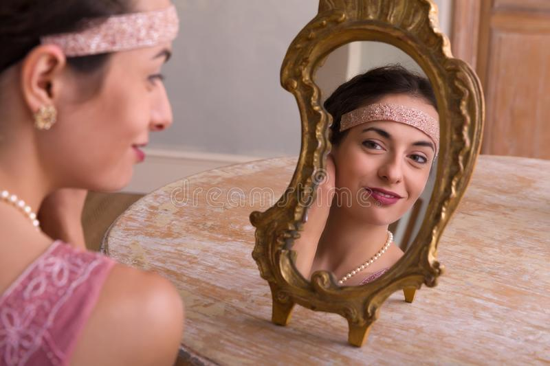 Elegant lady and antique mirror. Sensual young woman in 1920s flapper dress and headband looking in an antique mirror royalty free stock image