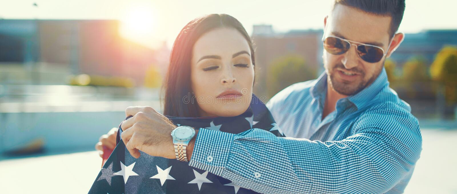 Sensual young woman covered by man with USA flag banner. Sensual young women covered by men with USA flag banner, outdoors royalty free stock photos