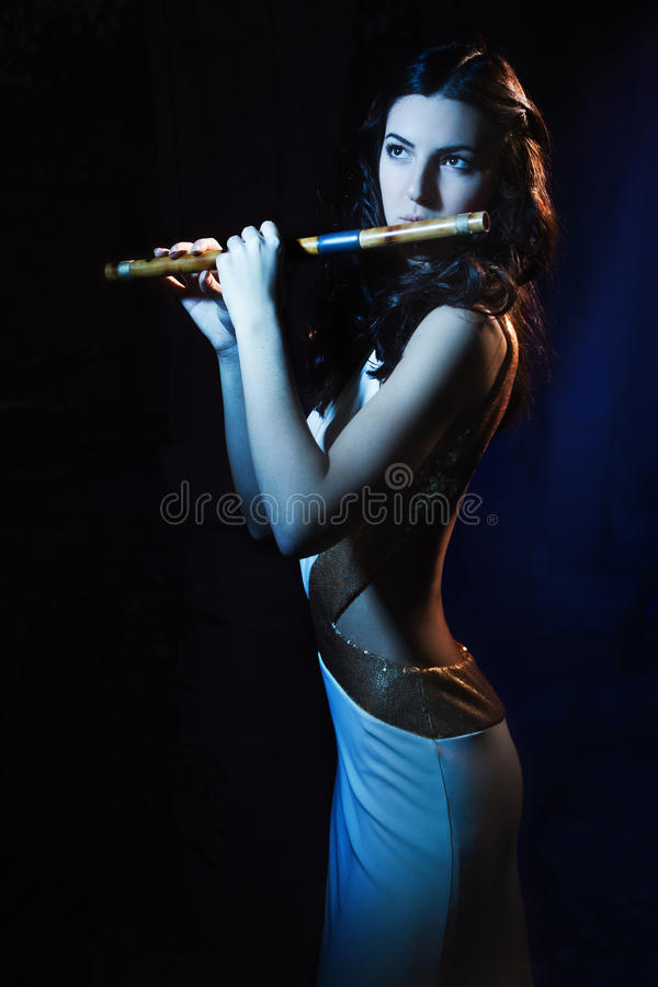 Download Sensuality Brunette Plays A Wooden Flute Royalty Free Stock Photography - Image: 28327597