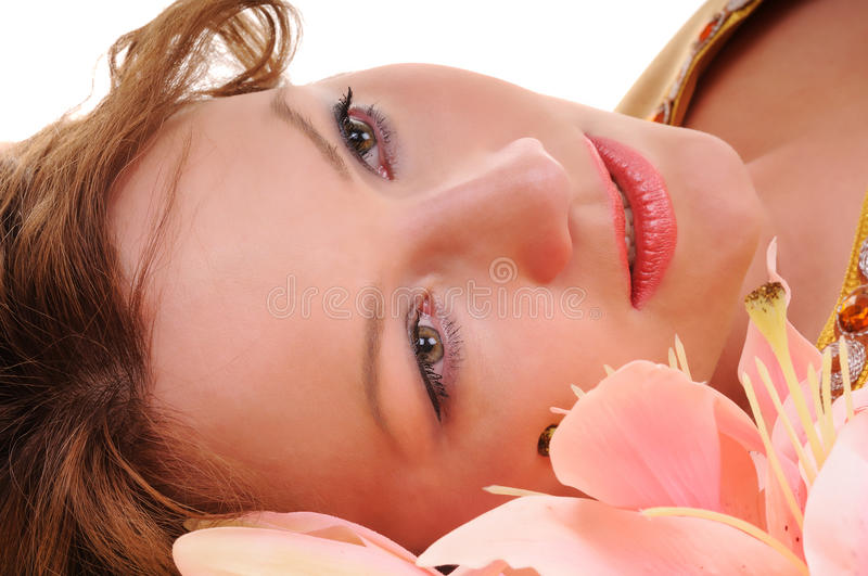 Sensuality glance. Close-up beauty woman face with lily flowers royalty free stock photo