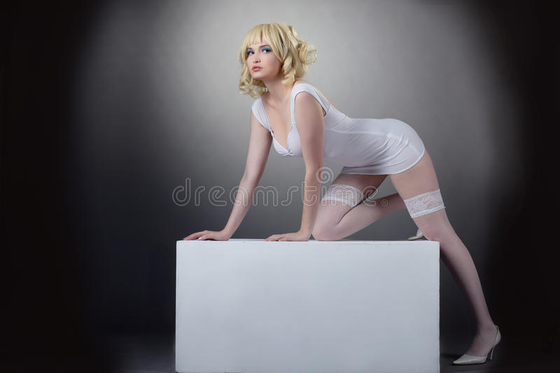 Sensuality potrait of pretty woman with cube. Sensuality potrait of pretty blond woman in white fashion cloth royalty free stock image