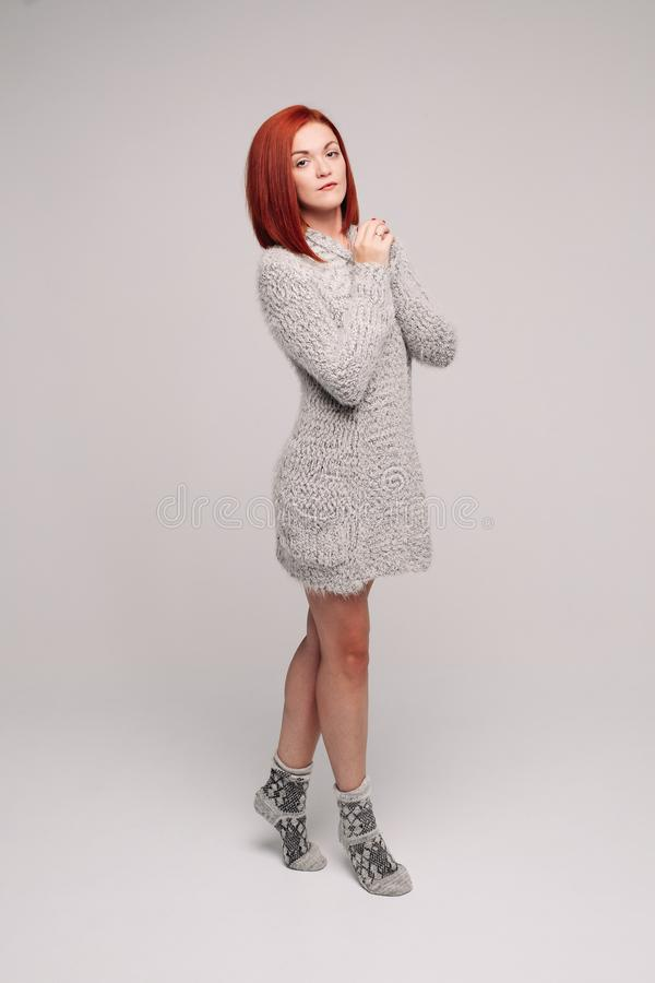 Sensuality red haired girl wearing gray knit sweater and warm socks. royalty free stock image