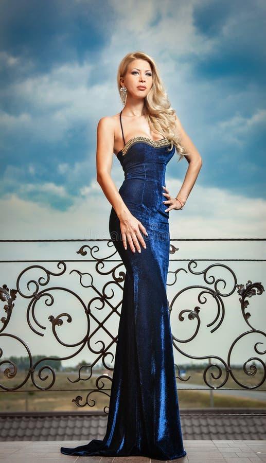 Sensueel blonde met blauwe kleding op richel stock foto