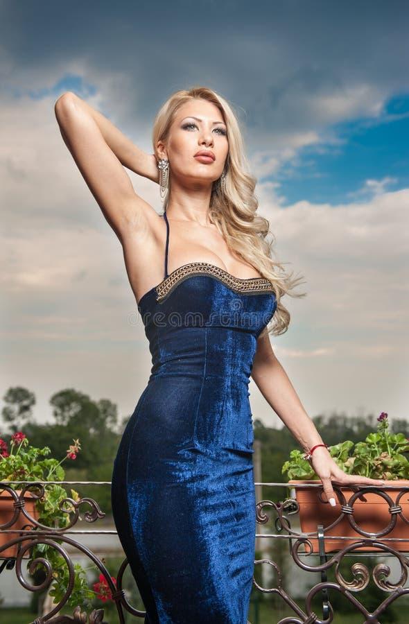 Sensueel blonde met blauwe kleding op richel stock afbeeldingen