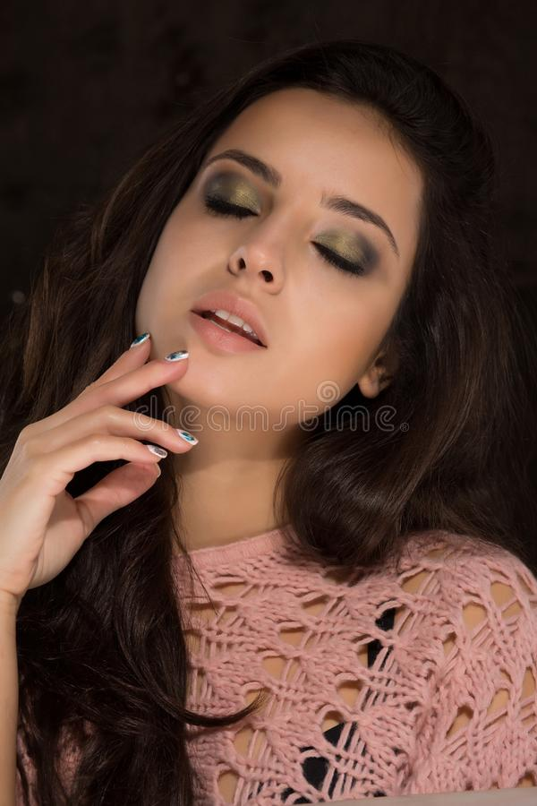 Sensueel donkerbruin model met professionele make-up in sweaterposin stock fotografie