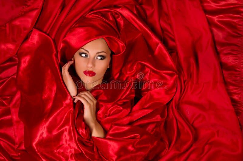 Sensueel gezicht in rode satijnstof stock afbeelding