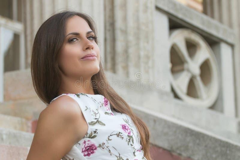 Sensueel jong donkerbruin vrouwenportret die in openlucht op treden zitten stock foto