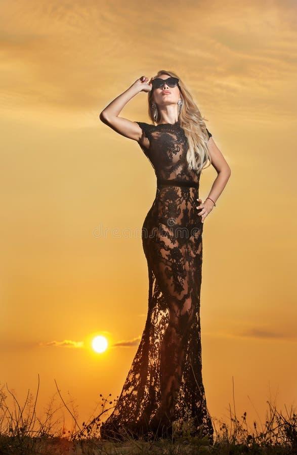 Sensueel meisje die met zon achter haar toenemen stock foto