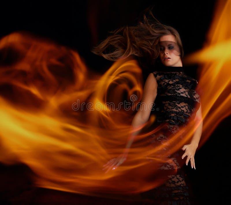 Sensueel meisje in zwarte kleding die met vlam danst royalty-vrije stock afbeelding