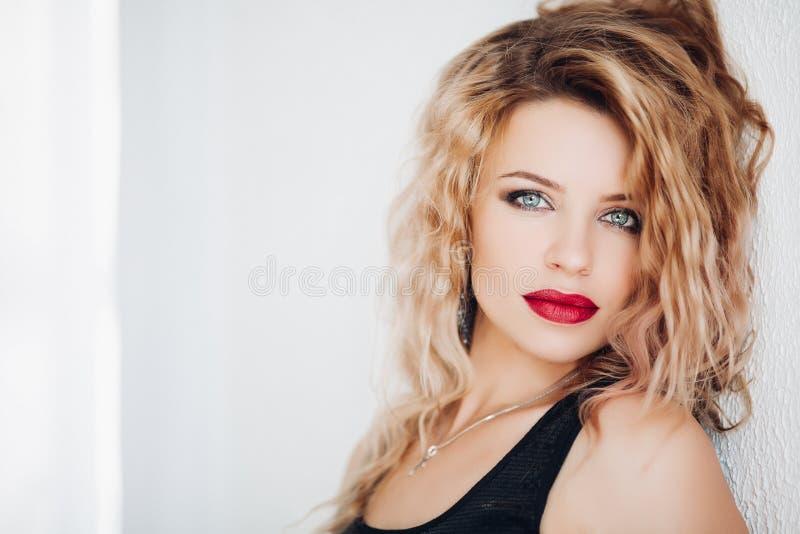 Sensueel model met golvend blondehaar en rode lippen die camera tegen witte achtergrond bekijken royalty-vrije stock afbeeldingen