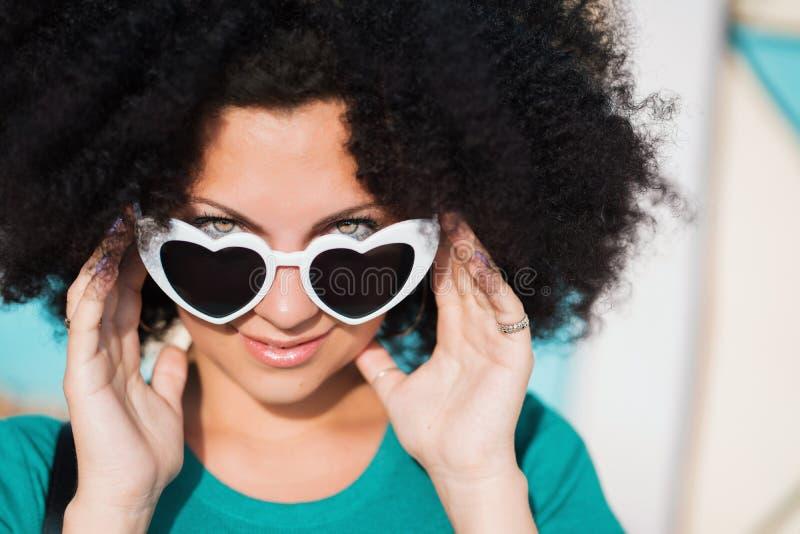 Sensueel portret van jonge mooie vrouw met Afrikaans krullend kapsel en hart-vormige zonnebril Mooi meisje met royalty-vrije stock afbeeldingen