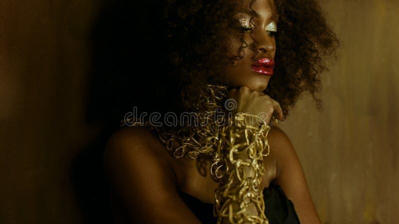 Sensueel portret van sexy Afrikaans Amerikaans vrouwelijk model met het glanzende gouden make-up stellen aan de camera op geweven stock foto's